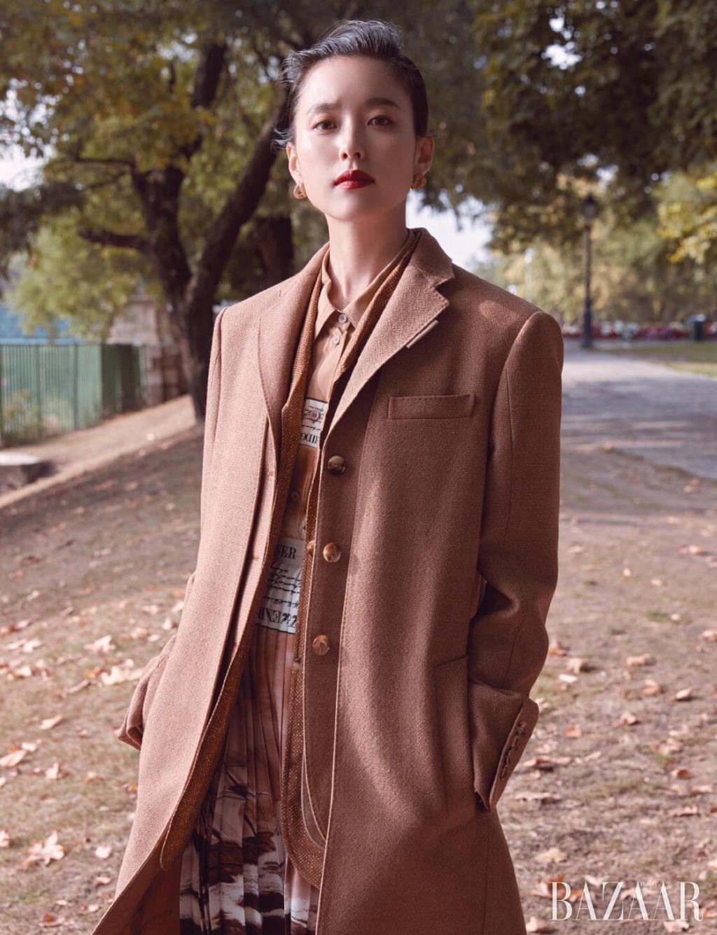 버튼 장식의 울 테일러드 코트, 피시 스케일 프린트 재킷, 이너로 입은 실크 셔츠, 플리츠 스커트, 스몰 체인 링크 귀고리는 모두 Burberry.