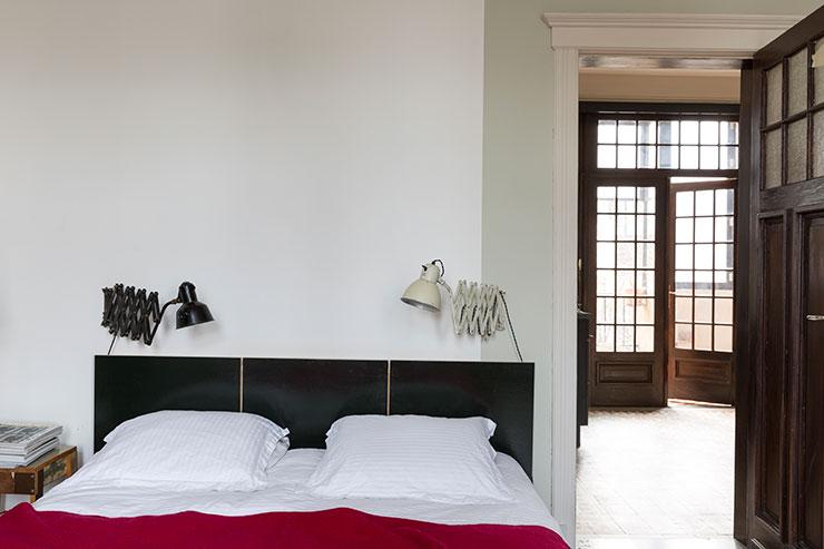 화이트 컬러와 페일 그린 컬러 페인트를 칠한 벽이 안락한 느낌을 주는 침실. 레드 컬러 담요와 길이 조절이 가능한 램프는 모두 빈티지 제품이다.