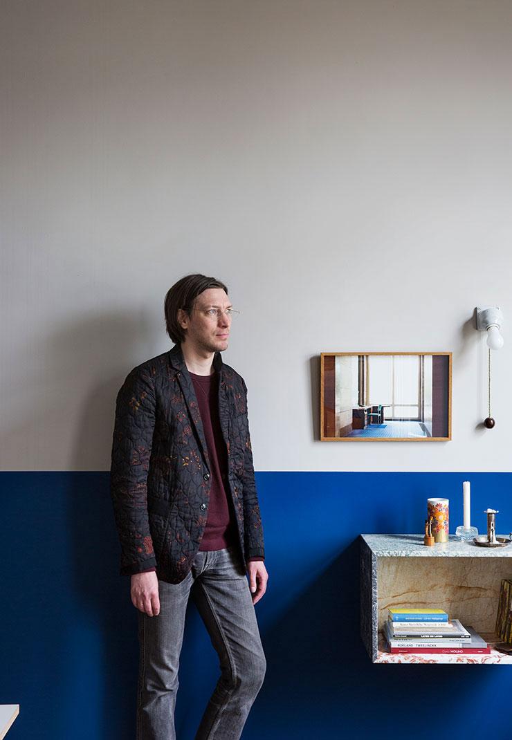 집주인 브레히트가 서재에 서 있다. 벽 하단은 벨기에 페인트 브랜드 에멘테(Emente)의 'Edo Blue' 컬러로 칠했다. 벽에 걸린 사진은 아네미 아우구스티인스(Annemie Augustijns)의 작품.