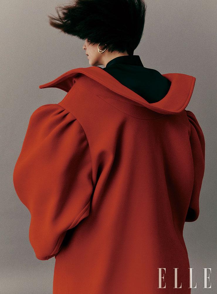 조형적인 골드 이어링과 블랙 실크 셔츠, 과장된 실루엣의 코트는 가격 미정, 모두 Balenciaga.