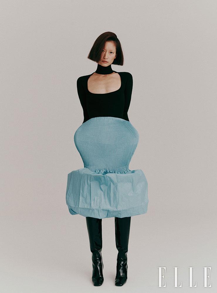 터틀넥 보디수트는 가격 미정, 파스텔컬러의 미디스커트는 2백63만5천원, 모두 Bottega Veneta. 스퀘어 토 롱부츠는 가격 미정, Prada.