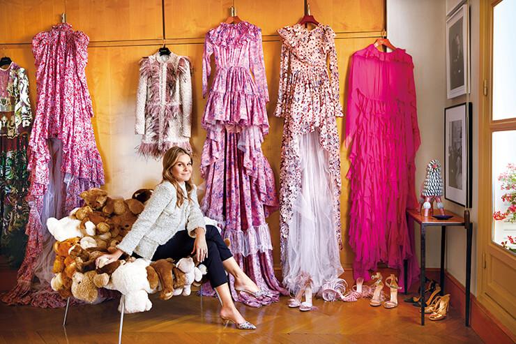 발렌티노와 지암바티스타 발리 드레스가 걸린 침실에서 샤넬 재킷과 프라다 팬츠를 입은 채 미소를 짓고 있는 에어린 로더.