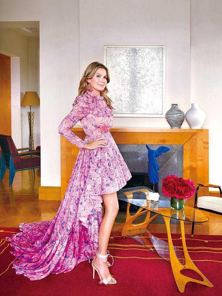 거실에서 지암바티스타 발리 드레스를 입고 서 있는 에어린 로더.