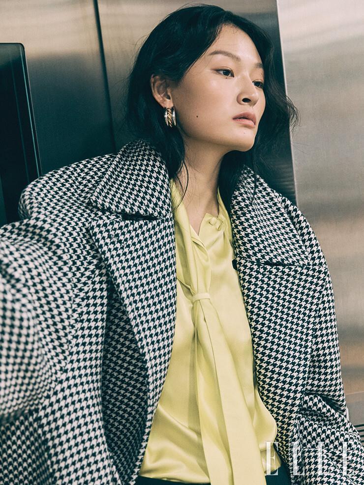 하운즈투스 체크 코트는 4백55만원, 보타이 장식의 실크 블라우스와 볼드한 이어링은 가격 미정, 모두 Balenciaga.
