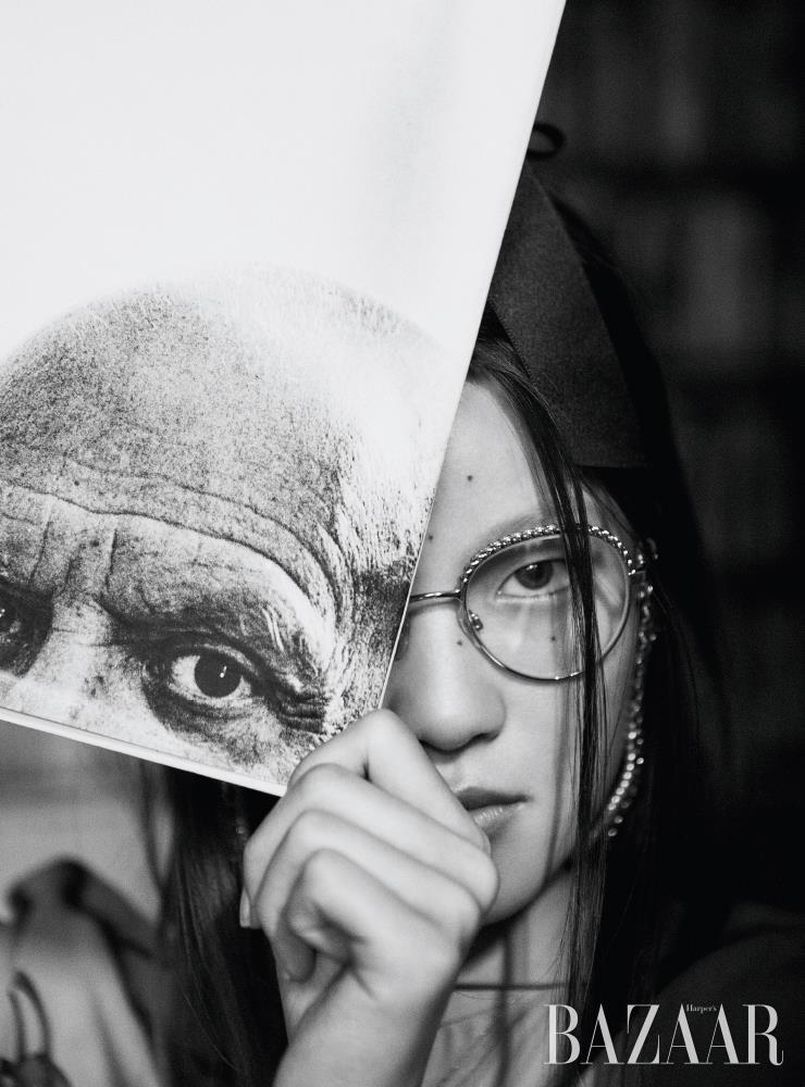 블라우스는 Hermès. 헤어 클립, 진주 체인 장식 안경은 모두 Chanel. 모델이 들고 있는 책은 'Portraits de Picasso. Jacques PRÉVERT', Éditions Ramsay, 1981.