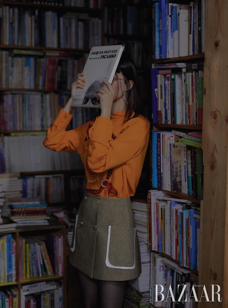 블라우스는 Hermès. 스커트는 Fendi. 헤어 클립, 진주 장식 체인 안경은 모두 Chanel. 타이츠는 에디터 소장품. 모델이 들고 있는 책은 'Portraits de Picasso. Jacques PRÉVERT', Éditions Ramsay, 1981.