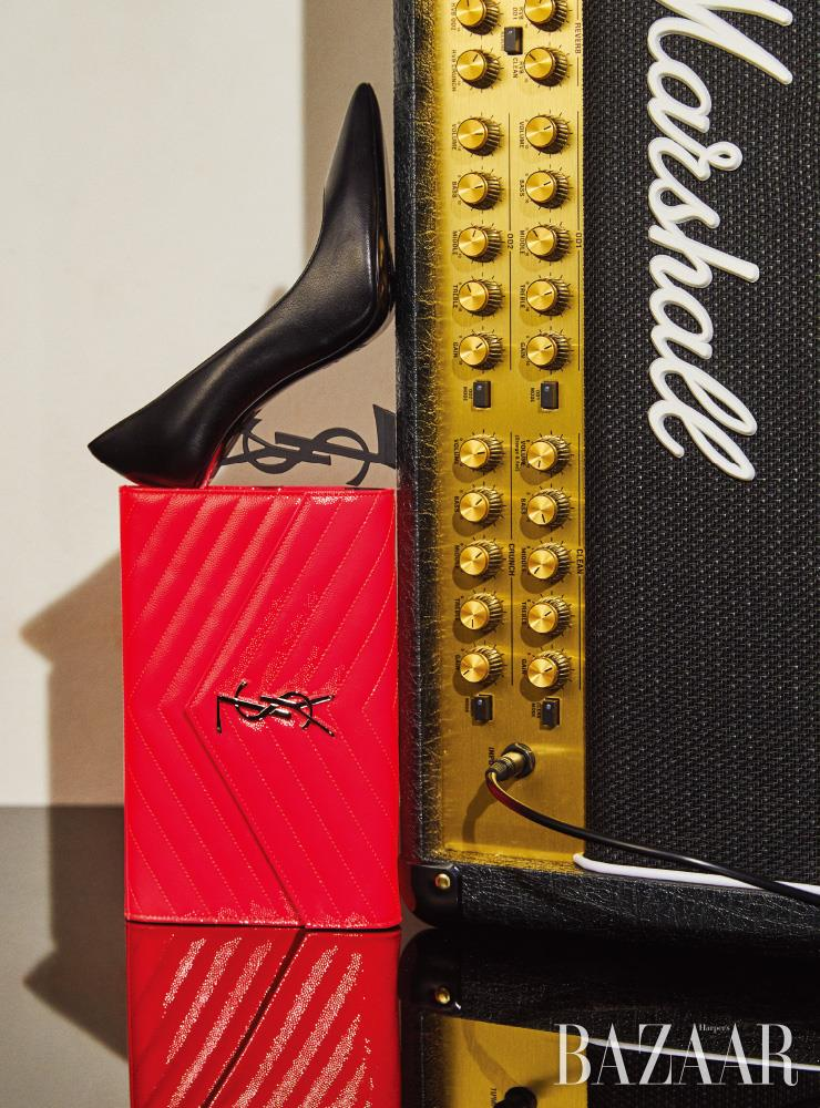 매트한 올 블랙의 '오피움' 펌프스, 네온 핑크 컬러의 지갑은 모두 Saint Laurent by Anthony Vaccarello.