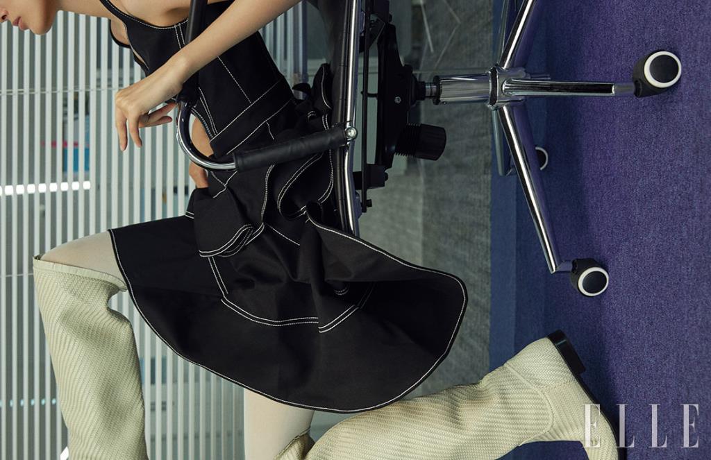 스티치 장식의 플레어 미니드레스는 Alexander McQueen. 화이트 롱 부츠는 Dior.