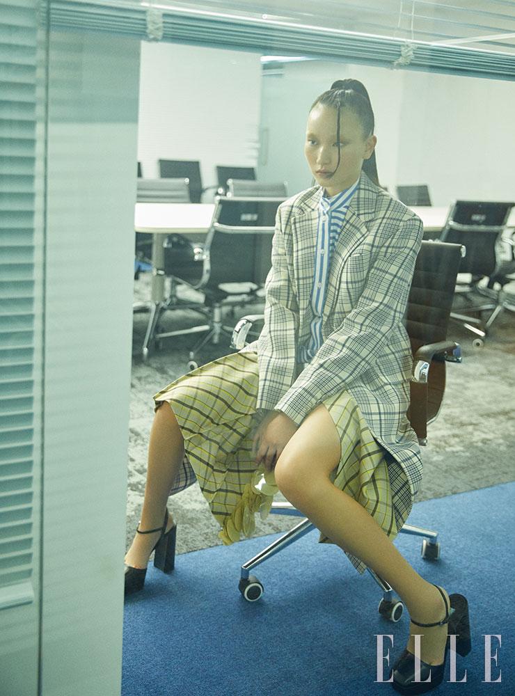 체크 코트와 스트라이프 셔츠, 슬릿 스커트, 플랫폼 스트랩 하이힐은 모두 Prada.