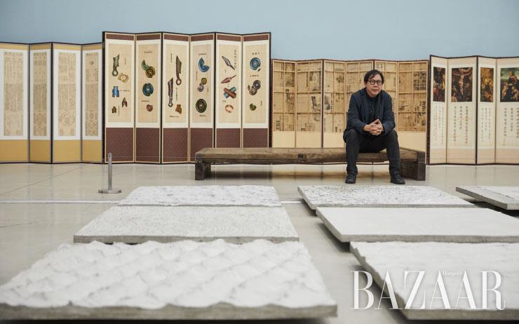 국립현대미술관 5전시실 중앙, 일종의 '마당'인 <해인>(2019)에 앉은 박찬경 작가. 16개의 시멘트에 물결 무늬를 새긴 작업으로, 세계의 만물이 도장으로 찍은 듯 바닷물에 뚜렷하게 비쳐 보인다는 불교 개념을 육중하고 단단한 시멘트 덩어리로 표현했다.