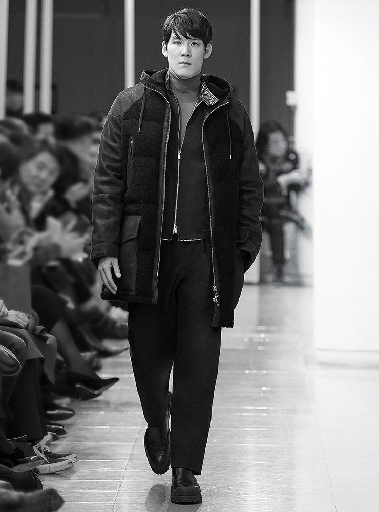 후드가 달린 무통 코트와 블루종, 블루 터틀넥 톱, 팬츠, 펀칭 부츠는 모두 Hermès.
