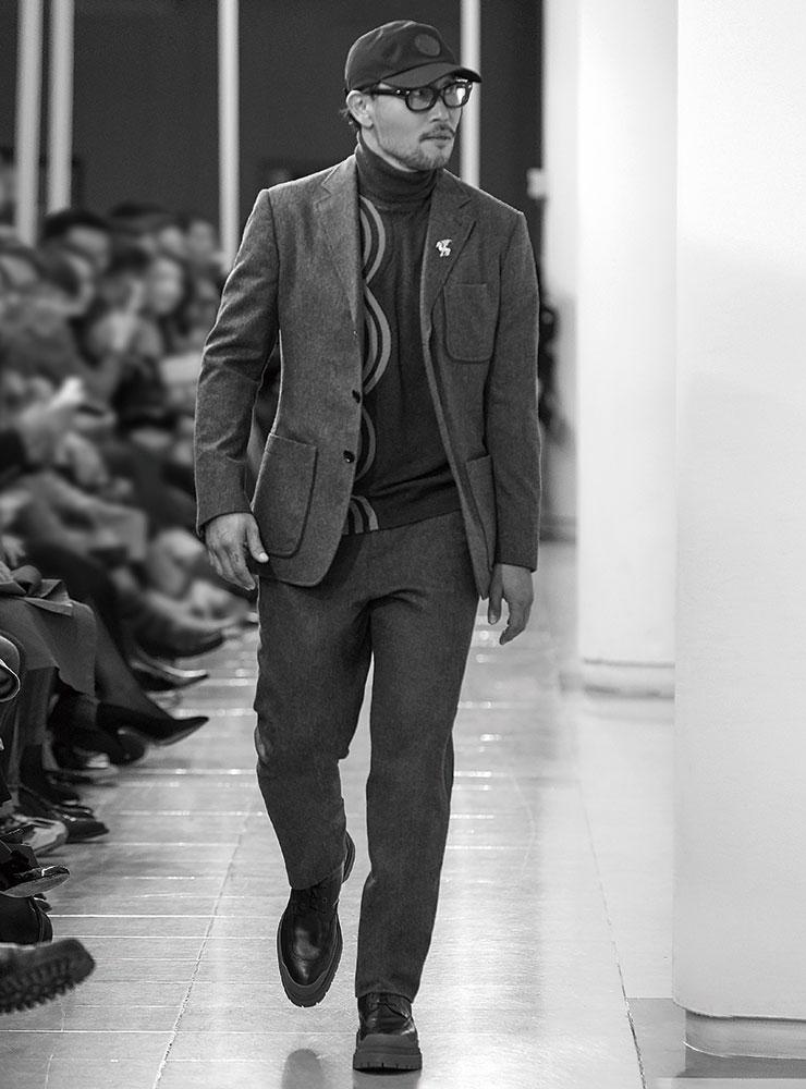 볼 캡과 파이핑 장식의 그레이 수트, 그래픽 패턴의 터틀넥, 러버솔 부츠는 모두 Hermès.
