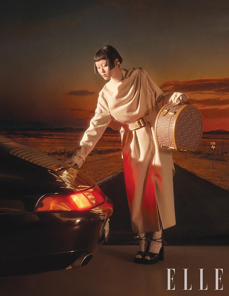 케이프를 두른 듯한 디자인의 코트와 비즈 장식이 돋보이는 레이스 글러브, 미키마우스를 새겨 넣은 트렁크 백, 화이트 타이츠, 플랫폼 힐, 진주 장식의 이어 커프는 모두 Gucci.