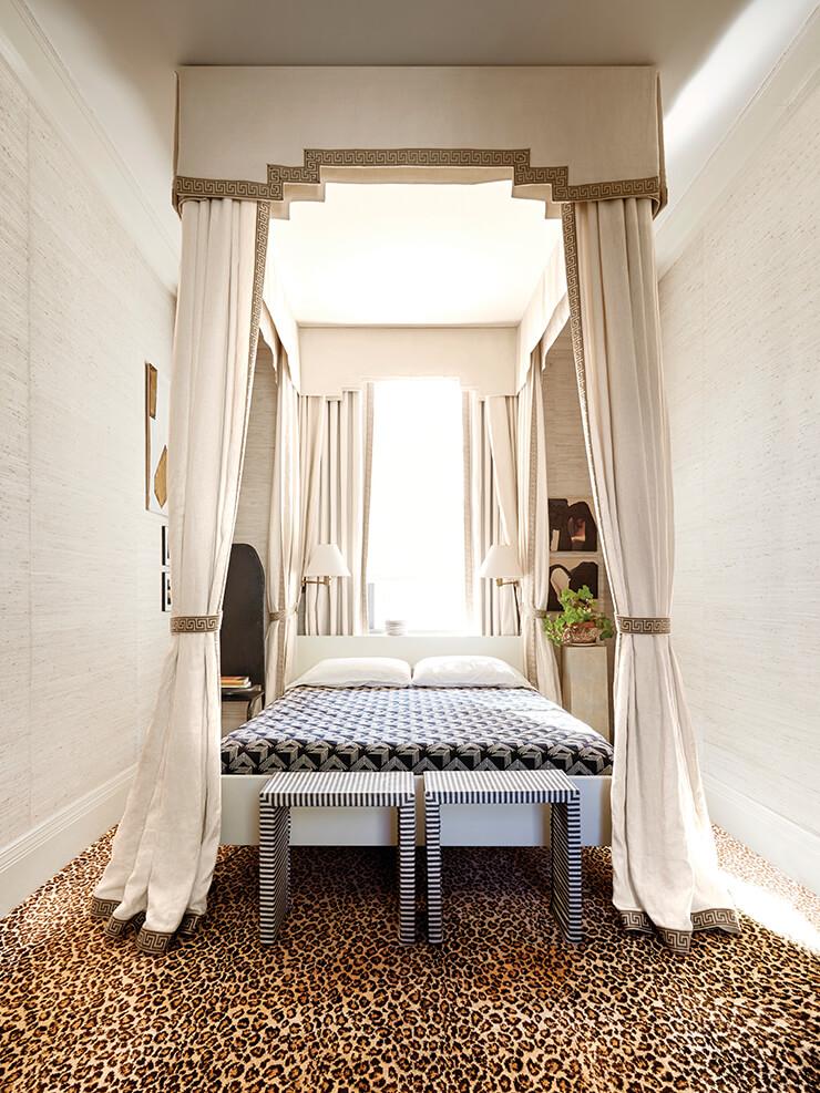 호피 무늬 카펫이 깔린 안방 침실. 천장의 트림에는 리넨 캐노피가 우아하게 매달려 있다.