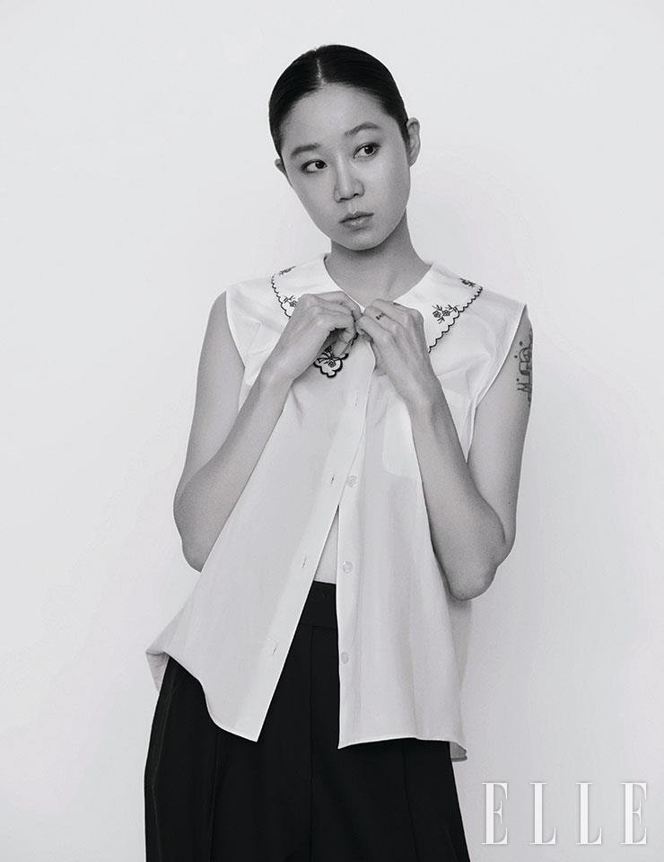 자수 디테일의 슬리브리스 셔츠와 팬츠는 모두 Miu Miu.