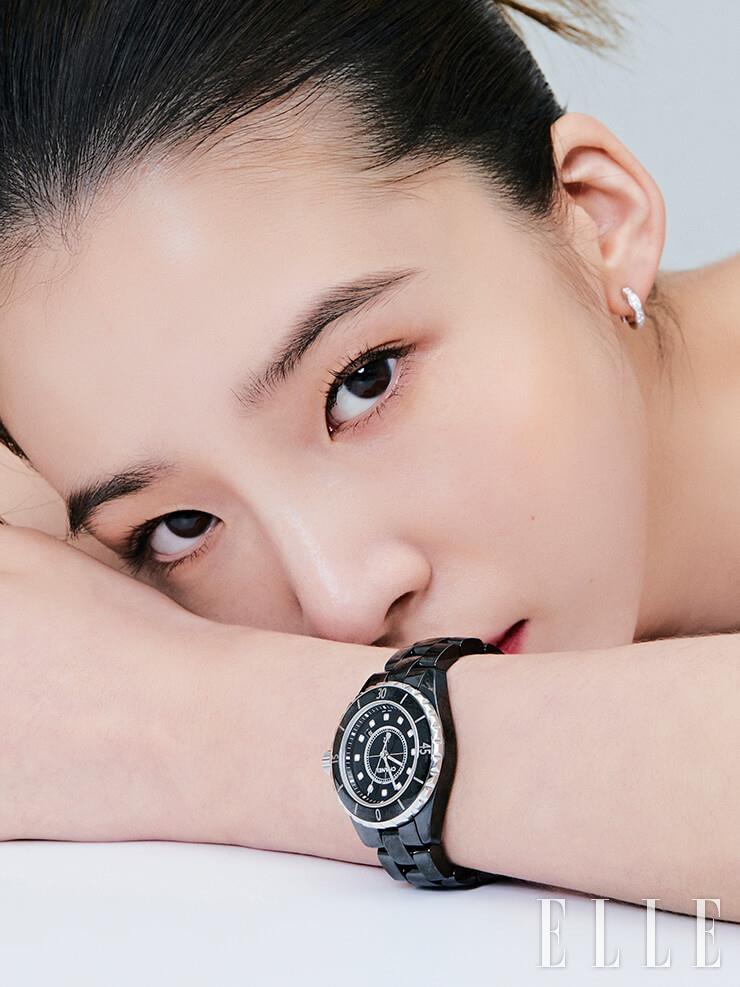 블랙 세라믹 케이스 위로 반짝이는 12개의 다이아몬드 인디케이터가 시선을 사로잡는 지름 33mm 버전의 J12 워치, 화이트골드에 브릴리언트 컷 다이아몬드가 세팅된 코코 크러쉬 이어링은 모두 Chanel Watches & Fine Jewelry.