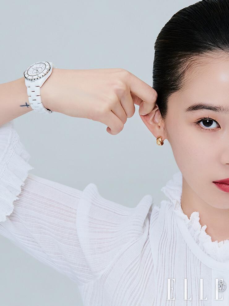 다이아몬드 인디케이터가 세팅된 지름 33mm의 화이트 J12 워치는 고정밀 쿼츠 무브먼트를 사용했으며 J12 모델 중 가장 클래식한 버전이다. 화이트 J12 워치와 볼드한 퀼팅 텍스처의 옐로골드 코코 크러쉬 이어링은 모두 Chanel Watches & Fine Jewelry.