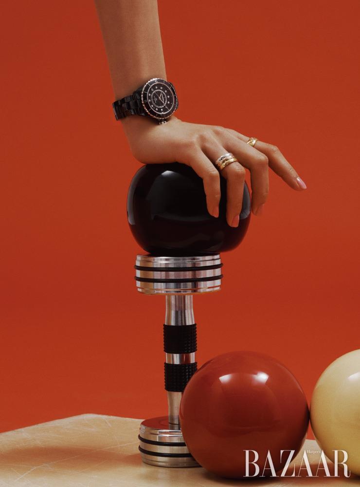 약 0.09캐럿의 다이아몬드 인디케이터가 세팅된 'J12 블랙' 워치, 검지에 낀 옐로 골드 '코코 크러쉬' 스몰 링, 약지에 레이어링된 화이트 골드, 베이지 골드, 옐로 골드 '코코 크러쉬' 슬림 링은 모두 Chanel Watches & Fine Jewelry.