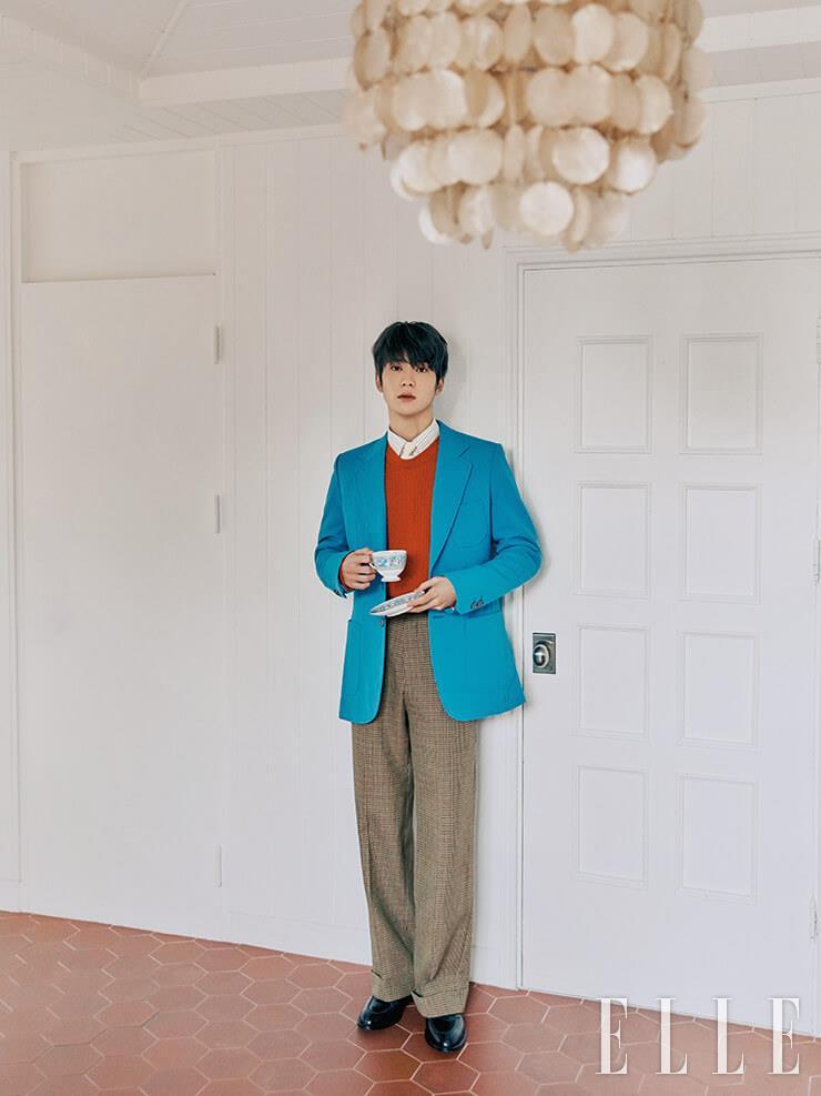 블루 재킷과 안에 입은 멀티 컬러 스트라이프 티셔츠, 레드 컬러 크루넥 스웨터와 팬츠는 모두 Gucci. 로퍼는 Alden. 타이는 COS. 벨트는 Ami. 손에 들고 있는 잔은 Wedgwood.