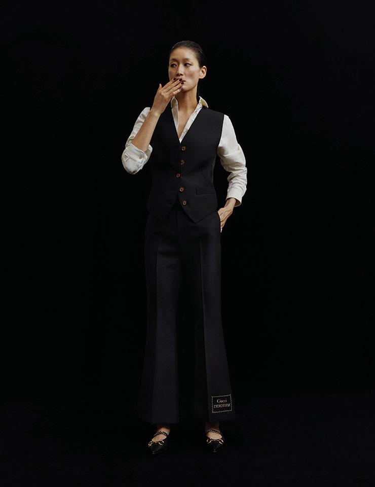 블랙 베스트와 팬츠, 화이트 셔츠, 홀스빗 로고 장식의 슈즈는 모두 Gucci.