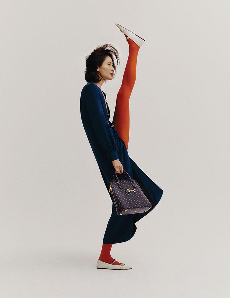 클리비지 라인이 돋보이는 맥시 드레스와 라텍스 소재의 롱 타이츠, 화이트 메리 제인 슈즈, 도트 무늬 '홀스빗' 톱 핸들 백은 모두 Gucci.