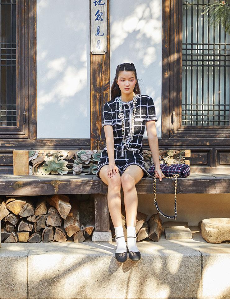 판타지 트위드 소재의 블랙 점프수트와 다채로운 스톤으로 완성한 롱 진주 네크리스, 클래식한 트위드 소재의 '19'백, 시퀸 플랫 슈즈는 모두 Chanel.