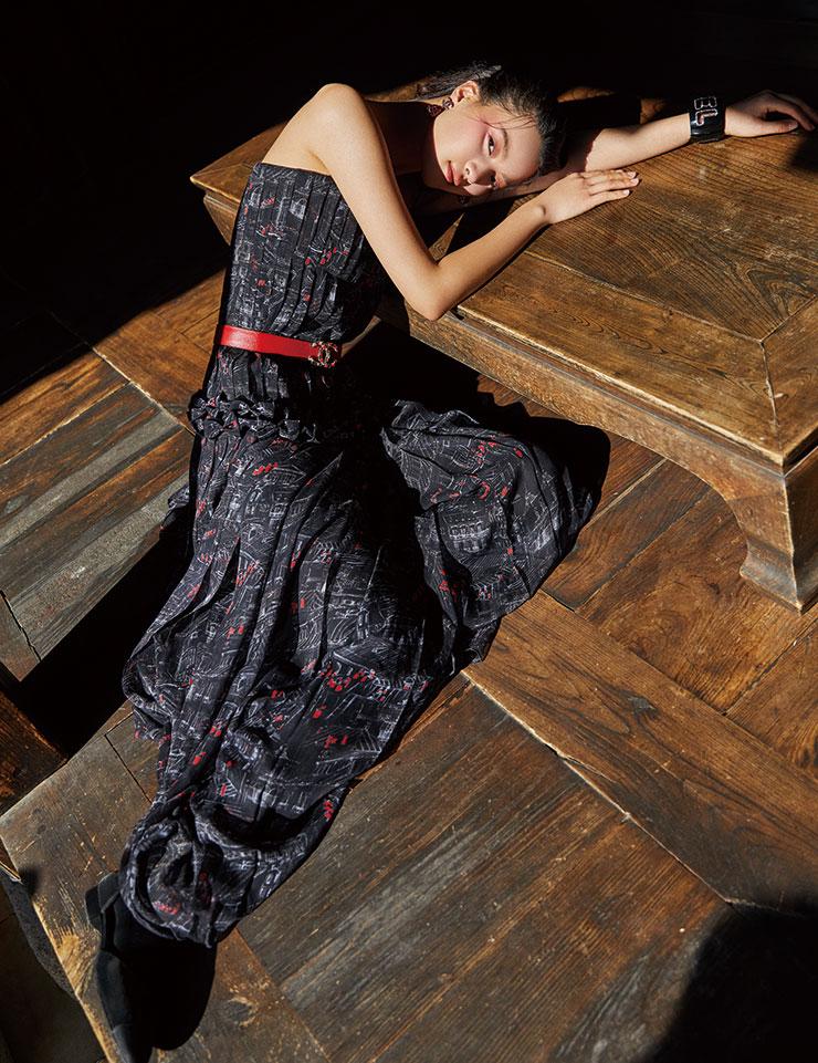 드로잉 프린트의 모슬린 롱 드레스, 로맨틱한 디자인의 레드 이어링, 로고 장식의 벨트, 볼드한 블랙 뱅글, 플랫 슈즈는 모두 Chanel.
