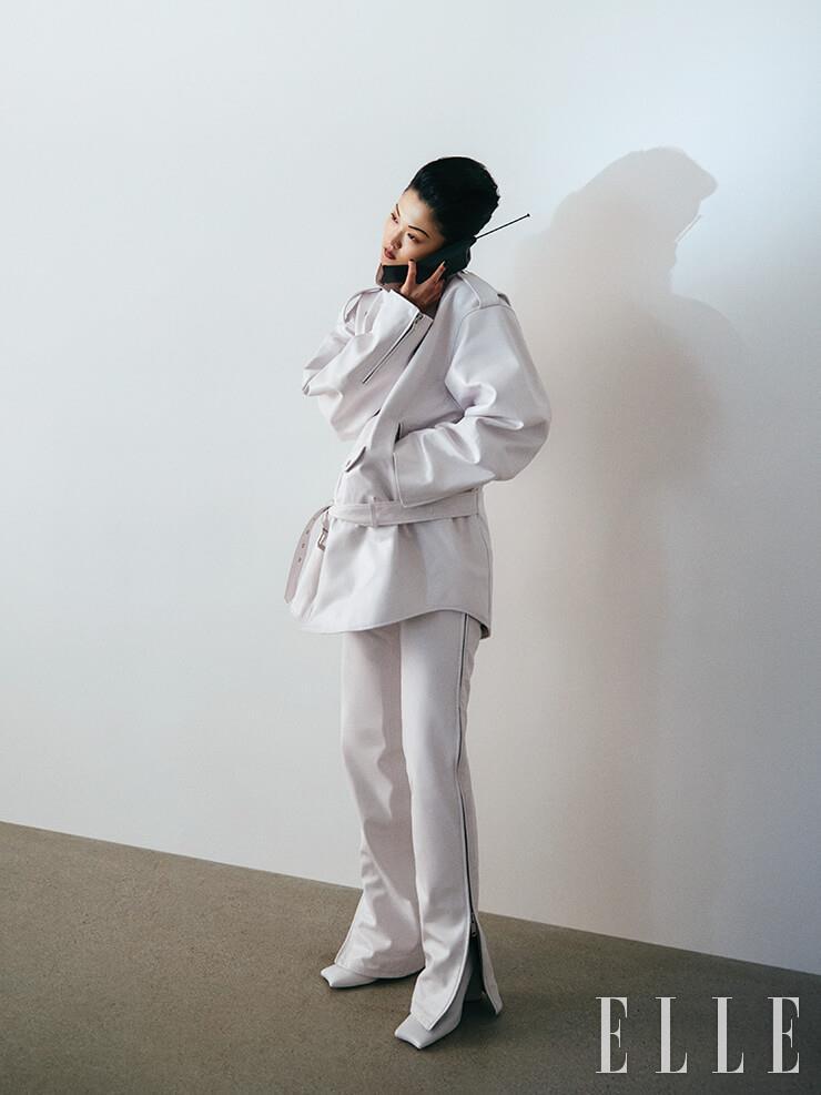 오버사이즈 바이커 재킷과 지퍼 여밈 장식의 화이트 팬츠, 스퀘어 토 앵클부츠는 모두 Balenciaga.