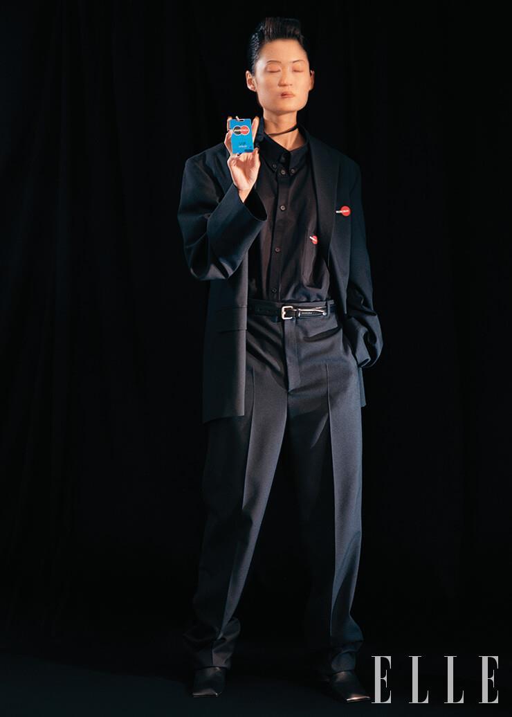 파워 숄더의 박시 재킷과 블랙 셔츠, 팬츠, 스퀘어 토 앵클부츠, 비지터 플레이트 네크리스, 레더 벨트는 모두 Balenciaga.
