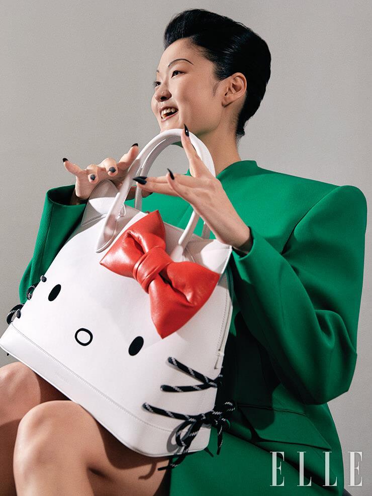 레트로 감성의 그린 컬러 재킷, 미니스커트, '헬로 키티 빌 탑 핸들 백'은 모두 Balenciaga.