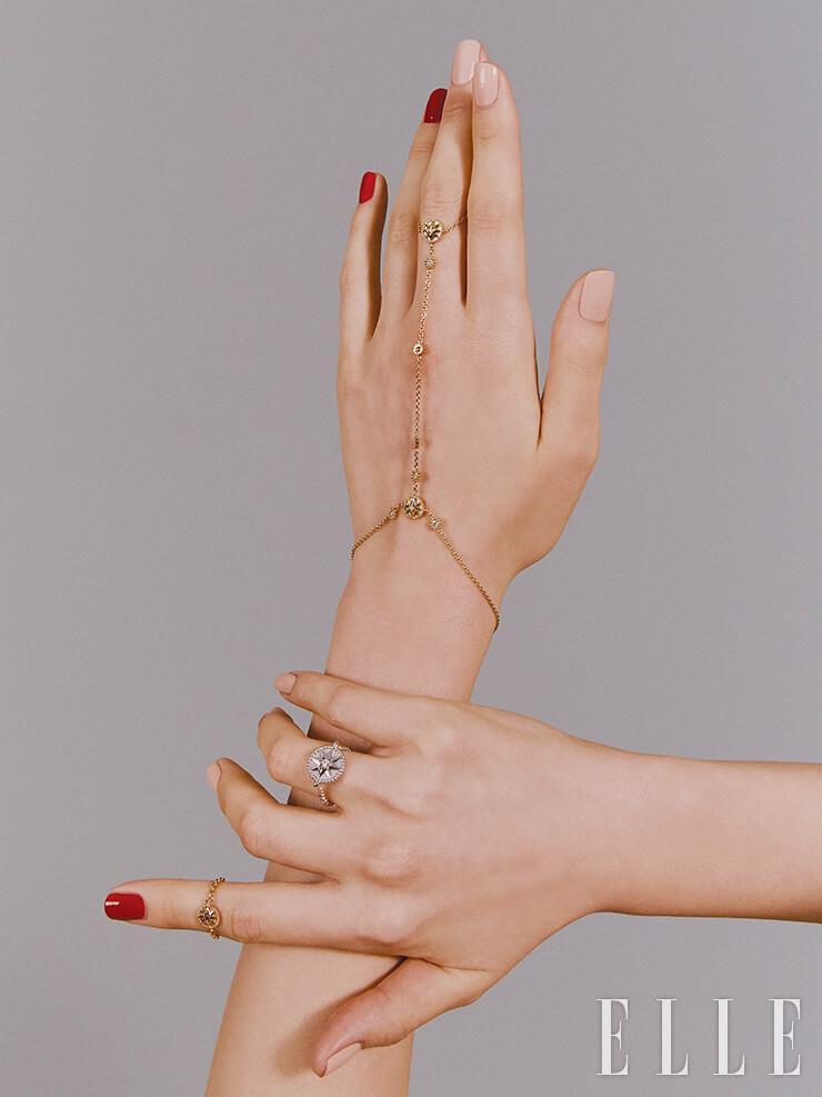 왼손에 낀 링과 브레이슬렛이 결합된 18K 옐로골드와 다이아몬드, 자개 장식의 로즈 드 방 핸드 주얼리, 오른손 검지에 낀 핑크골드와 루비를 세팅한 로즈 드 방 체인 링, 약지에 낀 18K 화이트골드와 다이아몬드 장식의 로즈 드 방 링은 모두 Dior Fine Jewelry.