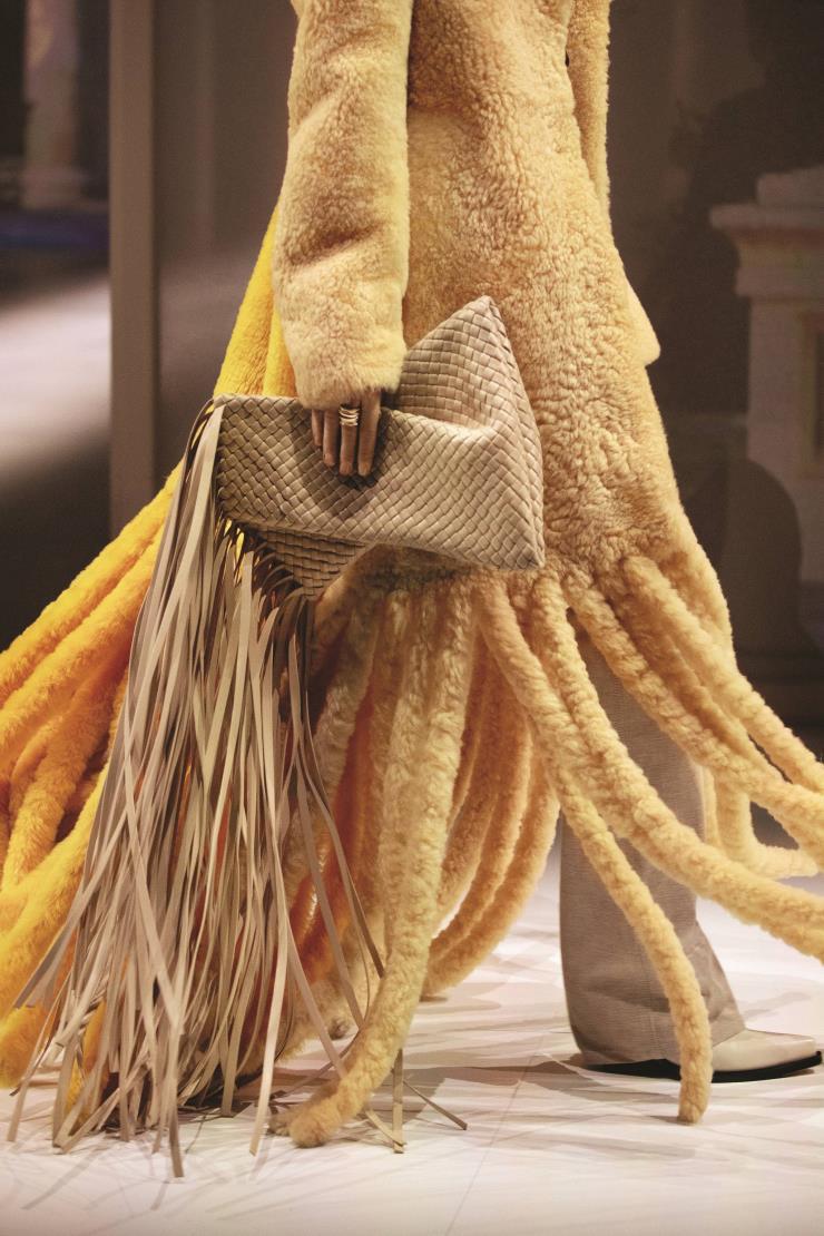 과감한 프린지 디테일의 룩과 핸드백.