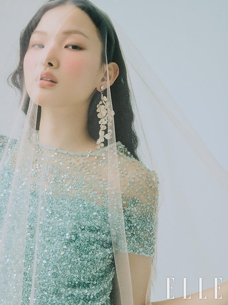 민트 컬러의 스팽글 드레스는 Escada Vintage Gown. 꽃 모티프의 싱글 이어링은 Angtt. 핑크 베일은 Esmeralda.
