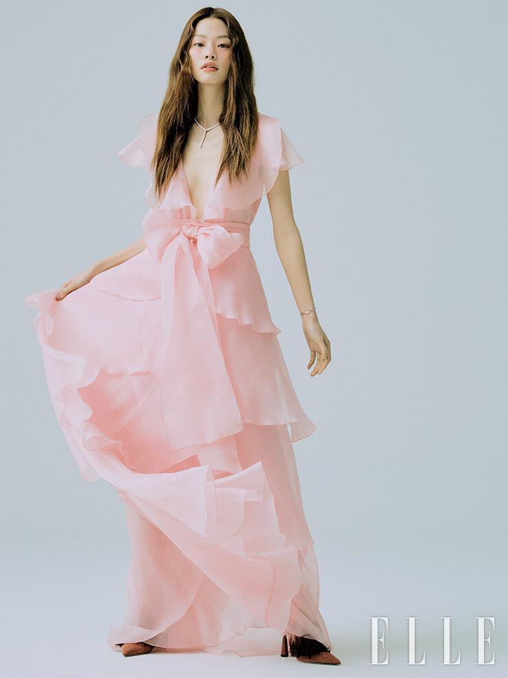시폰 소재의 핑크 티어드 드레스는 Blumarine. 뱀 모티프의 네크리스와 플라워 모티프의 브레이슬렛은 모두 Bvlgari. 링은 Cartier. 깃털 장식의 슈즈는 Jimmy Choo.