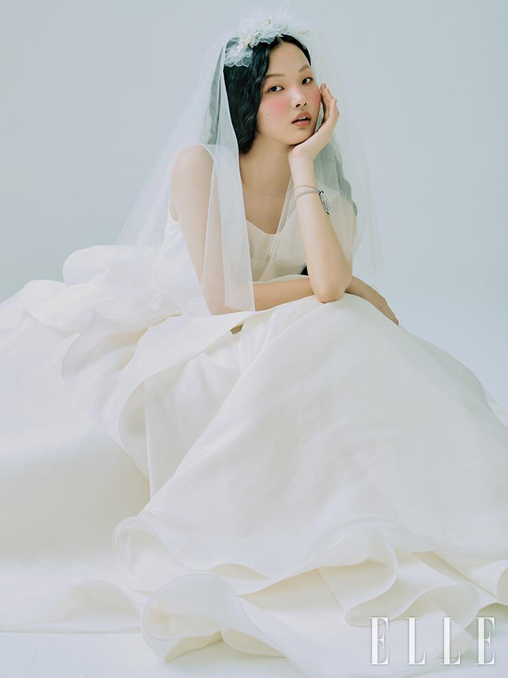 풍성한 실루엣이 우아한 드레스는 Antonio Riva by My Daughter's Wedding. 태슬 장식의 화이트골드 브레이슬렛은 Cartier. 쇼트 베일과 헤어 액세서리는 모두 Angtt.