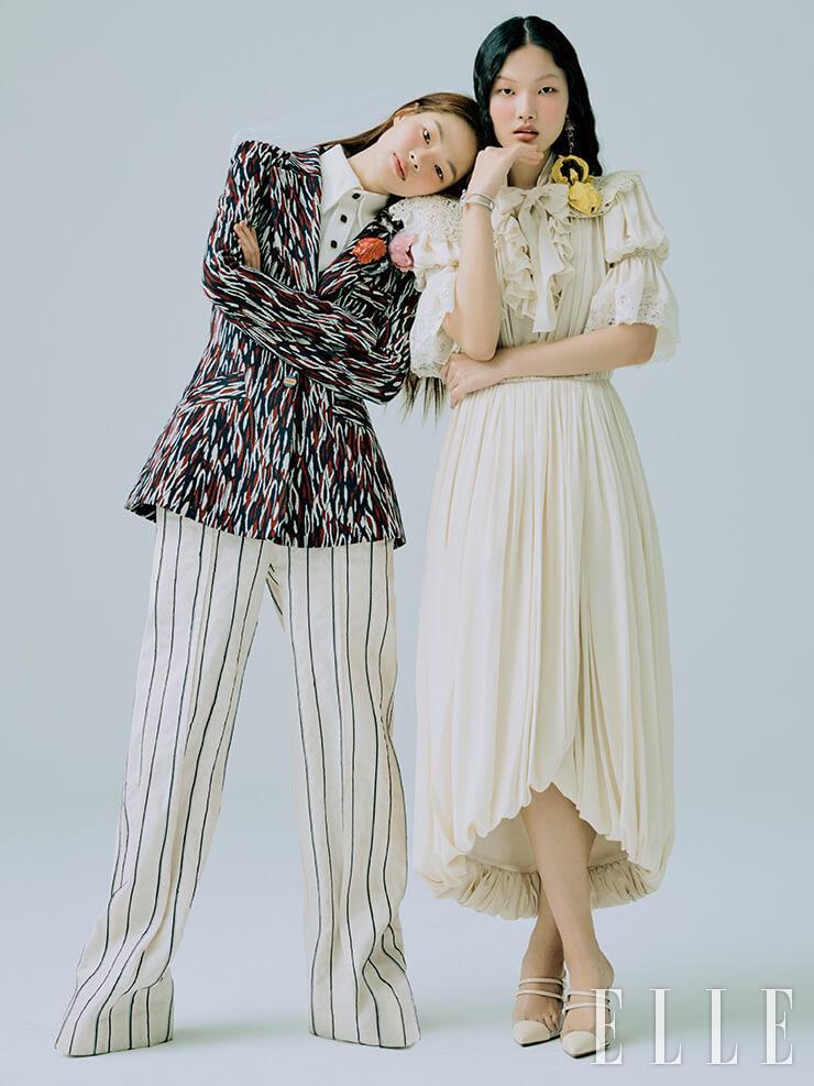 아현이 입은 그래픽 패턴의 재킷과 셔츠, 와이드 팬츠, 주향이 입은 퍼프 소매 드레스는 모두 Louis Vuitton. 컬러 스톤 드롭 이어링은 Monica Vinader. 다이아몬드 세팅의 꽃 모티프 브레이슬렛은 Bvlgari. 포인티드 토 뮬은 Aquazzura by Hanstyle Shoe.