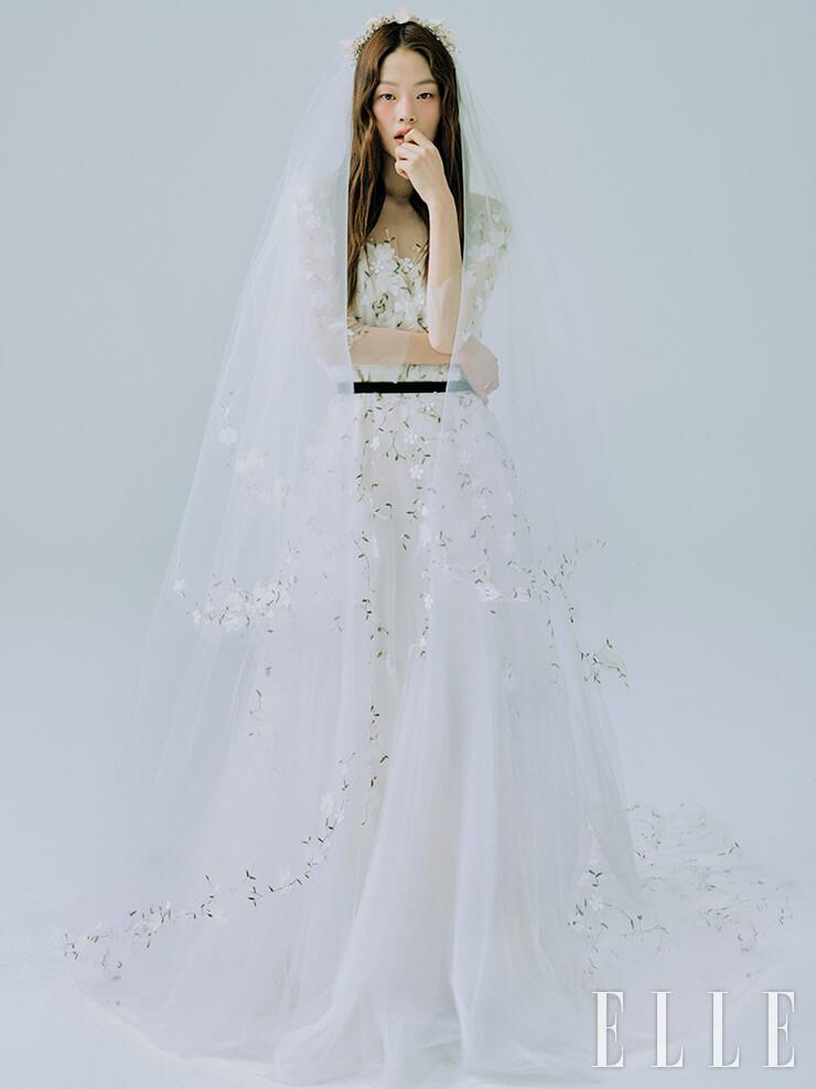 수수한 플로럴 디테일의 드레스와 베일은 모두 Leemyungsoon Wedding. 헤어피스는 Sooya.