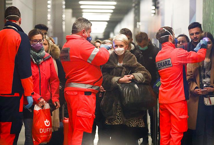 2월 26일 밀라노에서 출발해 폴란드에 도착한 항공기 승객들이 폴란드 보건 요원들로부터 체온 검사를 받고 있다.