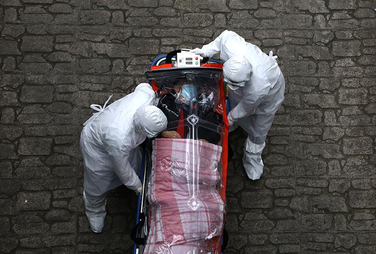 3월 9일 한국 의료진이 확진자를 앰뷸런스에서 병상으로 이송하고 있다. 이미 한국은 2월 23일 감염병 위기 경보를 '심각' 단계로 격상한 바 있다.