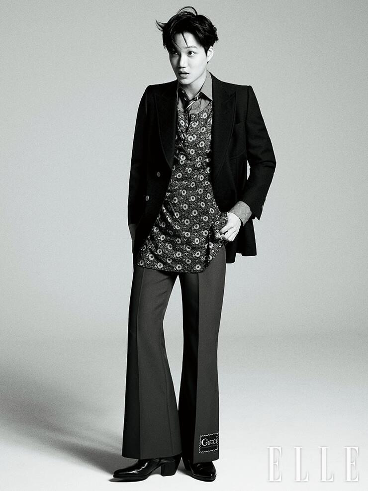 더블 브레스티드 재킷과 플로럴 프린트 톱, 레이어드한 셔츠, 스트라이프 패턴의 타이, 부츠 컷 팬츠, 앵클부츠는 모두 Gucci.