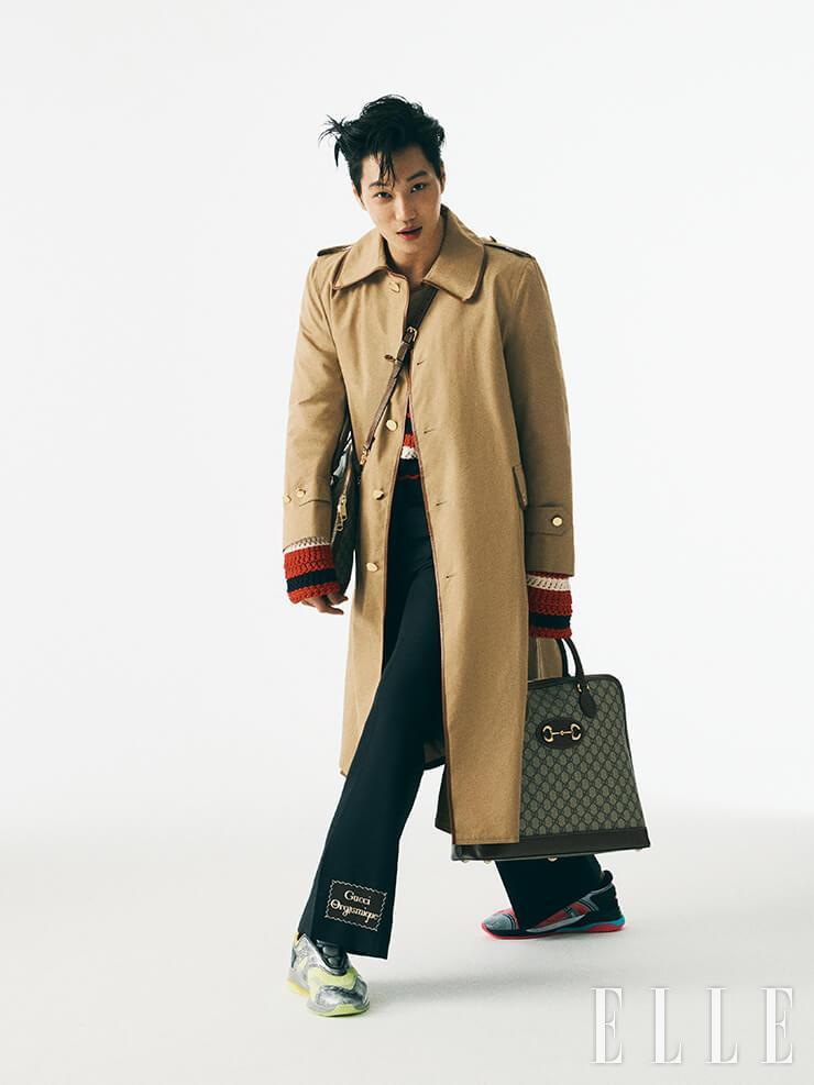 트렌치코트와 레드 컬러 니트 톱, 로고 장식의 부츠 컷 팬츠, GG 로고 패턴의 1955 홀스빗 백, 양쪽이 다른 컬러의 스니커즈는 모두 Gucci.