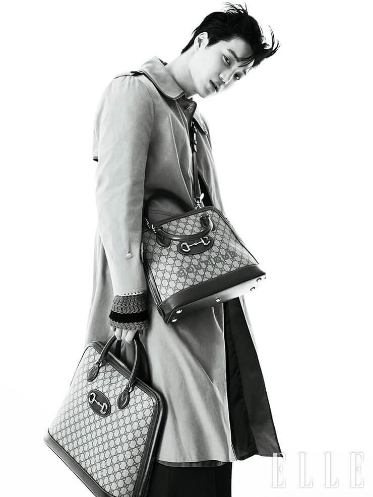 견장 디테일의 트렌치코트와 니트 톱, 블랙 팬츠, 레터링이 가미된 크로스백과 GG 로고 장식 1955 홀스빗 백은 모두 Gucci.