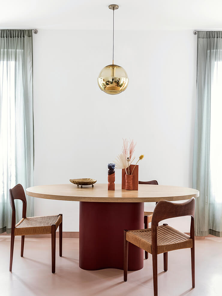 직접 디자인한 타원형의 묵직한 떡갈나무 테이블이 자리한 다이닝 공간. 테라코타 색을 칠한 테이블 다리가 눈에 띈다. 테이블 주변에는 여러 시대의 의자들이 조화롭게 어우러진다. 50년대 북유럽 의자와 70년대 빈티지 펜던트 조명은 juliebarrau.com. 테이블에 놓인 '큄' 꽃병은 Emmanuelle Roule.