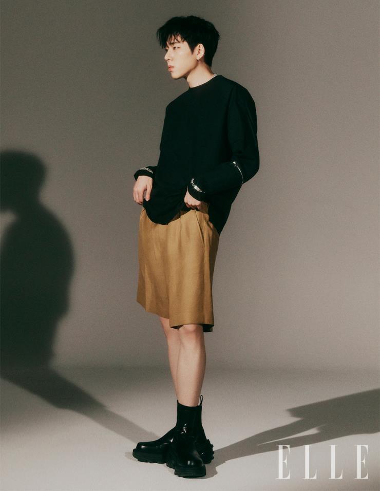 지퍼 디테일이 있는 블랙 긴팔 티셔츠, 베이지 컬러의 코튼 쇼츠는 모두 System Homme.