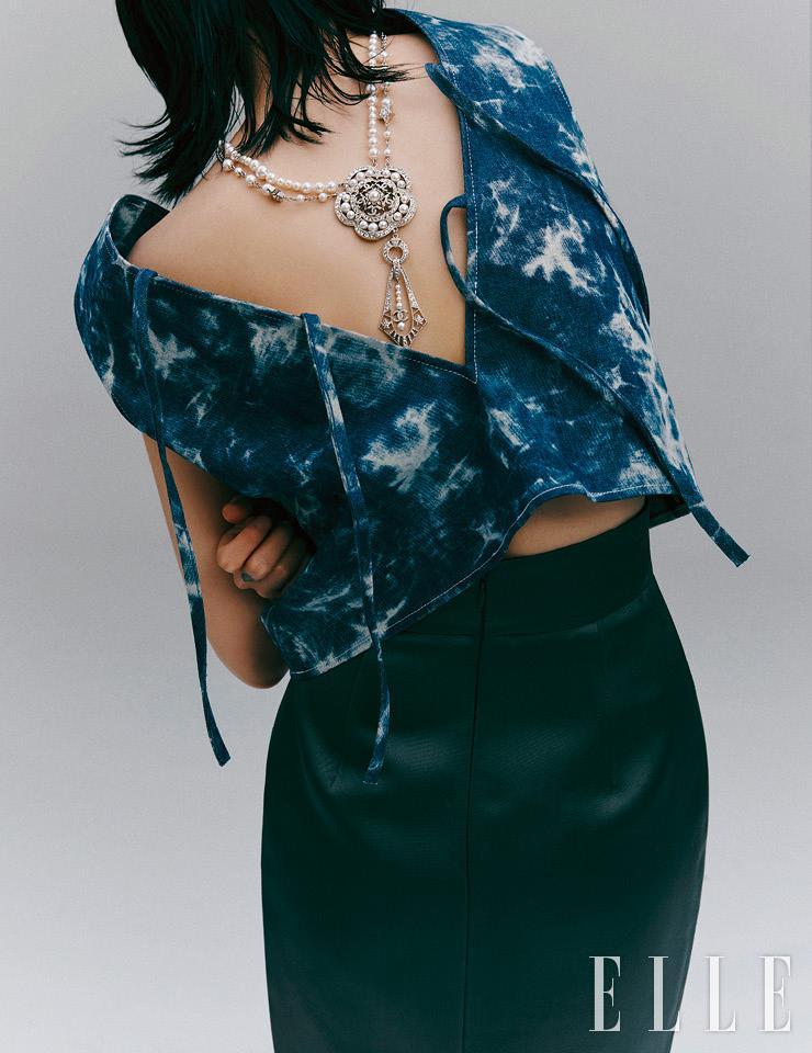 워싱 데님 소재의 베스트는 19만7천원, Neul. 카멜리아 펜던트 네크리스는 가격 미정, Chanel. 새틴 소재의 H라인 스커트는 가격 미정, Miu Miu.