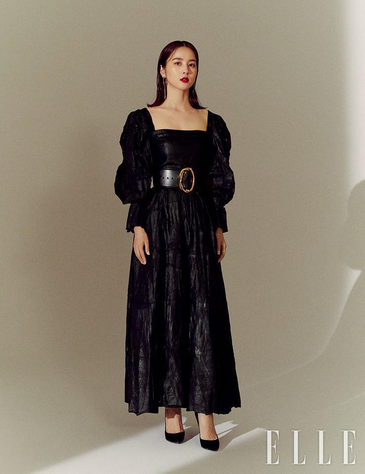볼륨있는 실루엣의 블랙 드레스와 벨트, 이어링은 모두 Alexander McQueen. 블랙 스틸레토 힐은 Gianvito Rossi.