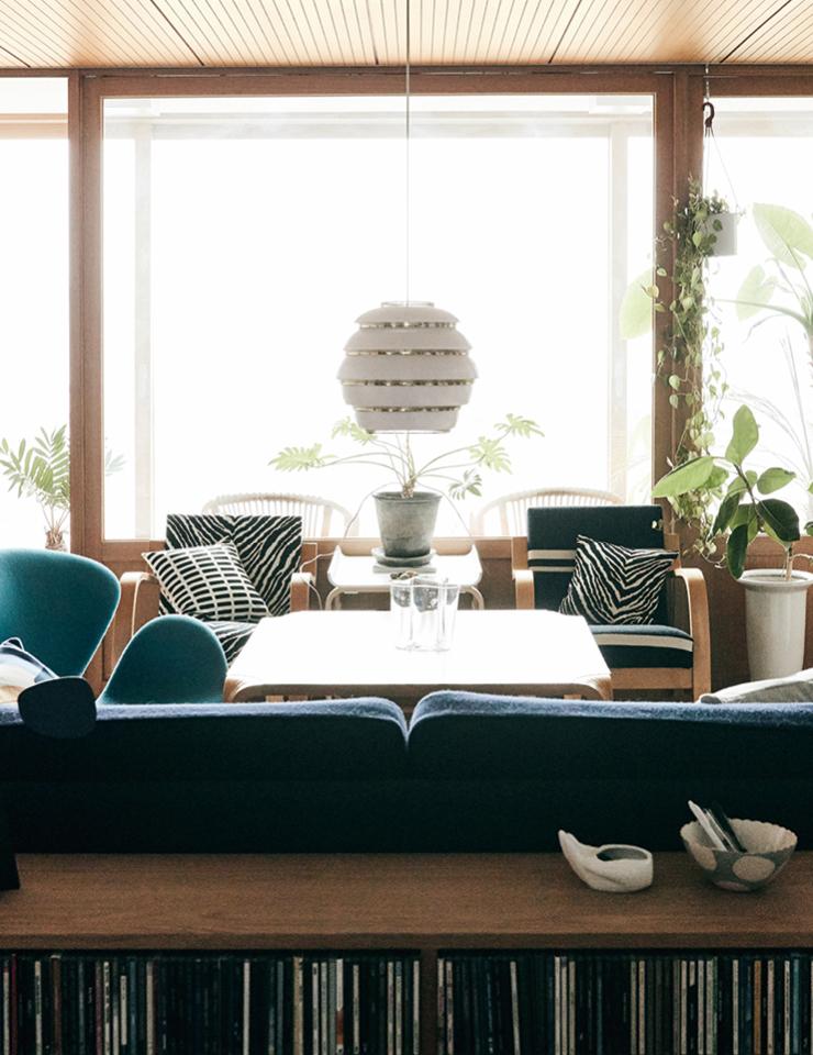 원래 확장형 집이었으나 식물을 키우고 테라스를 가지고 싶어 베란다를 만들었다. 소파와 테이블 모두 알바알토가 디자인한 가구들. 바다가 연상되는 푸른색 '스완 체어'는 Arne Jacobsen. 펜던트 조명 '비 하이브'와 소파는 Artek.