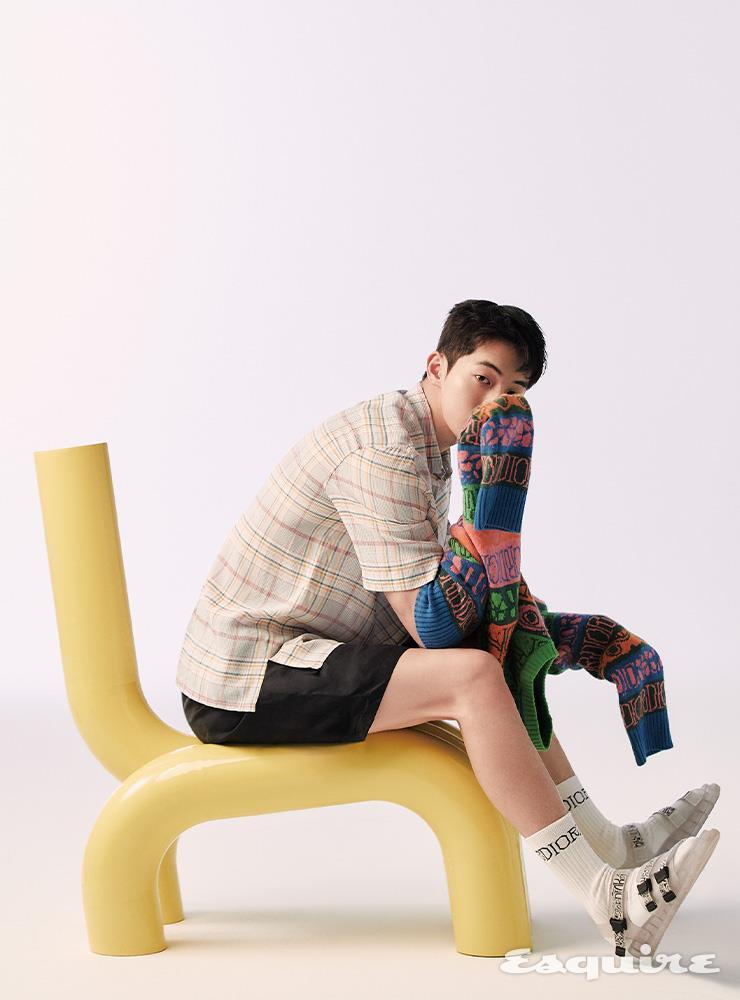 멀티컬러 캐시미어 니트, 오간자 소재 체크 반소매 셔츠, 네이비블루 버뮤다 쇼츠, 화이트 삭스, 반투명 솔을 단 아쿠아 샌들 모두 디올 맨. 노란색 의자 스툴 365.