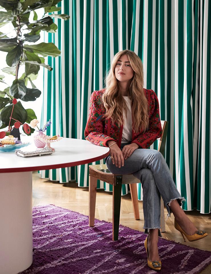 색색의 옷과 신발들이 즐비한 홈 오피스에서 포즈를 취한 에밀리 신들레프. 뒤에 보이는 커튼은 맞춤 제작했다.