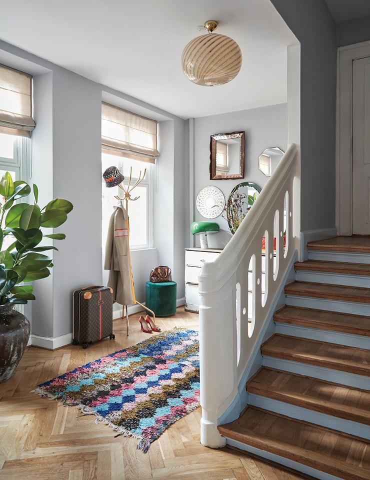 벽면에 칠한 연보라색 페인트가 은은히 빛나는 입구. 계단은 연한 푸른색으로 칠했다. 천장의 전등은 무라노(Murano)에서 만든 것으로, 전원을 켜면 벽 쪽에 줄무늬가 비친다. 카펫은 몇 년 전 헤이(Hay)가 연 빈티지 팝업 스토어에서 구입했다.